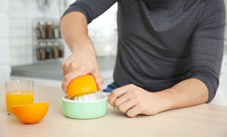 Young man making orange fresh on kitchen