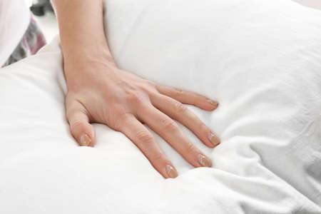 Female hand on orthopedic pillow, closeup