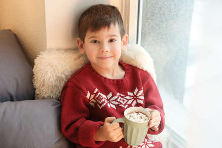 Cute little boy drinking hot chocolate with marshmallow while sitting on window sill at home