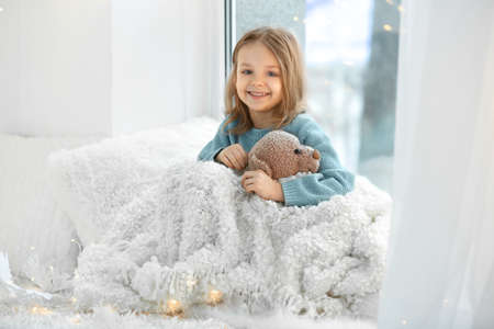 Cute little girl with teddy bear sitting on window sill at home Stock Photo
