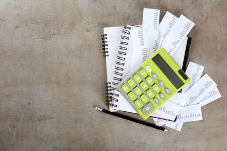 Green calculator with bills and notebook on gray background. Tax concept Stock Photo - 97529885