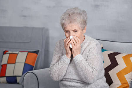 Mature ill woman with tissue at home. Concept of allergy