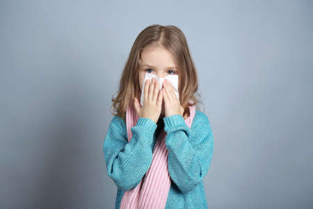 Small ill girl with napkin on grey background