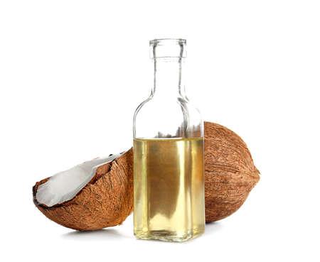 Botella con aceite de coco derretido y nuez sobre fondo blanco.