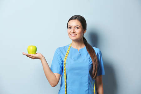 Female nutritionist with apple on light background