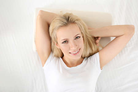 Young woman lying on orthopedic pillow in bed Stock Photo