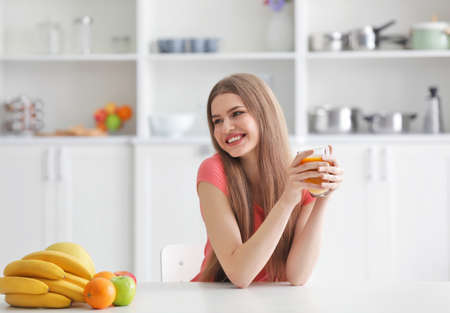 Young woman tasting fresh juice at kitchen