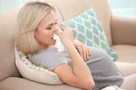 Pregnant woman with allergy sitting on sofa at home