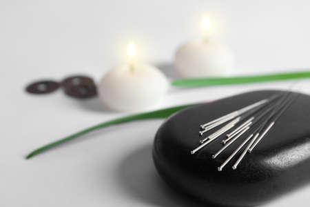 ライト付きキャンドルの上に鍼針のセットがぼやけた黒いスパストーン