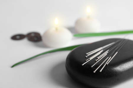 Black spa stone with set of acupuncture needles on lighted candles blurred background