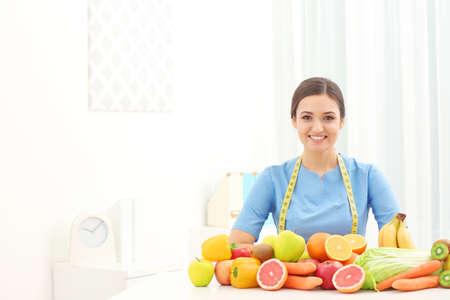 Nutritionniste féminine avec différents fruits et légumes au bureau Banque d'images - 97530010