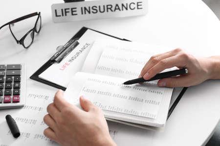 Levensplanning concept. Handen van verzekeringsagent op de werkplek