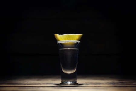 Tequila shot with juicy lemon slice and salt on dark background Stock Photo
