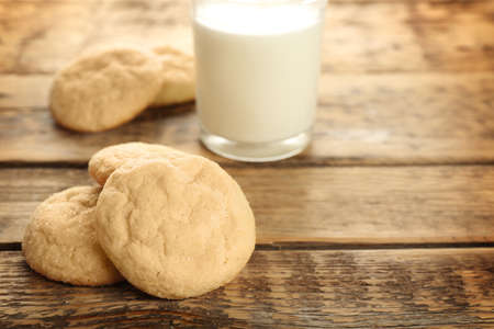 Tasty sugar cookies with glass of milk on table Stock Photo