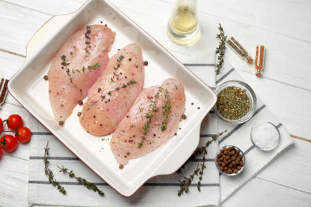 Raw chicken breasts with spices in baking dish on table