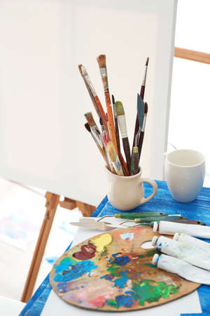 Cup with artist accessories on table