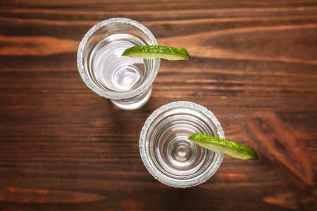 Tequila shots with juicy lime slices and salt on wooden background Standard-Bild