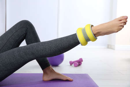 Woman training with weight on leg in gym