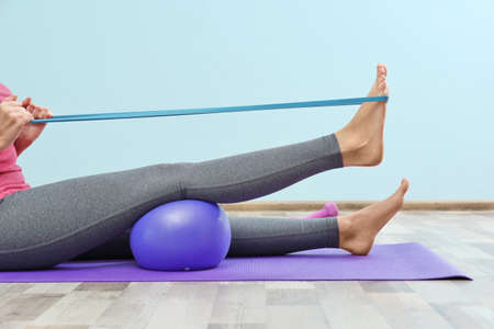 Woman training with elastic band in gym Stock Photo