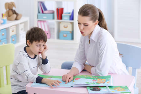 Cute little boy reading book at speech therapist office