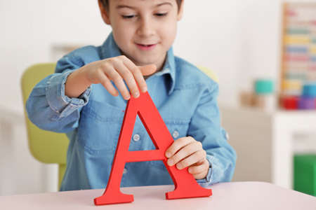 Cute little boy with letter A at speech therapist office