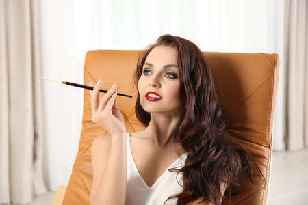 Beautiful woman smoking cigar while sitting in arm-chair indoors
