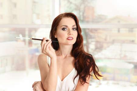 Beautiful woman smoking cigar indoors Stock Photo