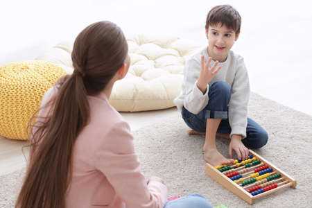 Cute little boy learning to count at private teachers office