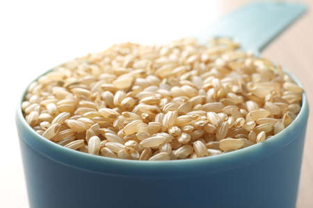 Measure scoop with brown rice closeup Stock Photo