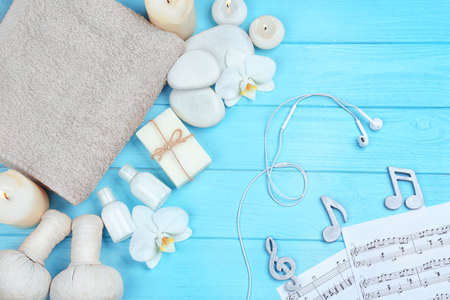 Beautiful composition of spa accessories and musical notes on blue wooden background
