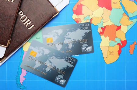Credit cards with passports and tickets for vacations on world map background