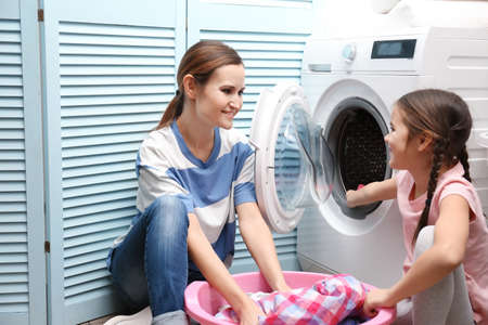 Mother and daughter loading clothes into washing machine