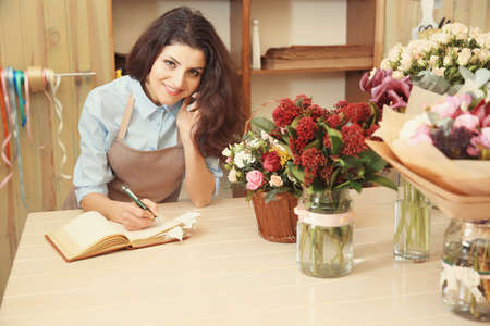 Beautiful woman florist using mobile phone while writing on notebook in flower shop