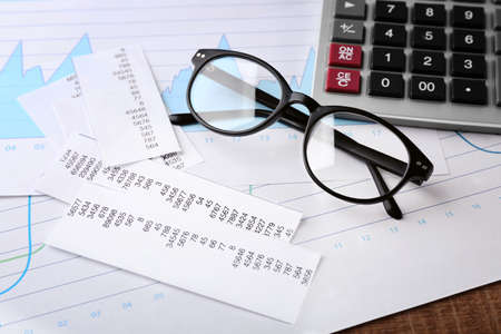 Calculator with documents and glasses on table. Tax concept
