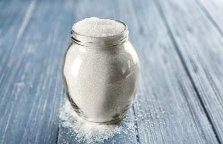 Glass jar full of sugar on wooden background