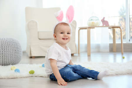 Cute little baby in bunny ears sitting on floor at home