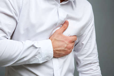 Heart attack concept. Young man suffering from chest pain on grey background Stock Photo