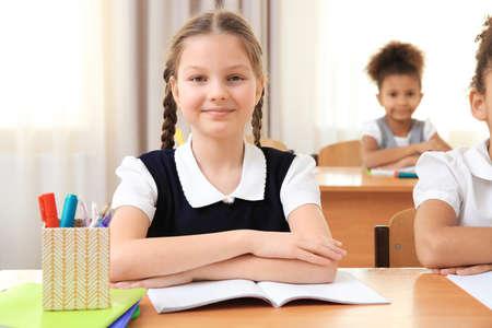 Portrait of beautiful elementary schoolgirl sitting in classroom
