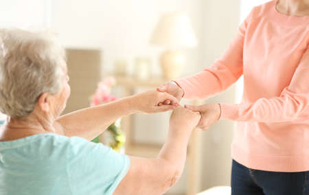 Old and young women holding hands on blurred background Stock Photo