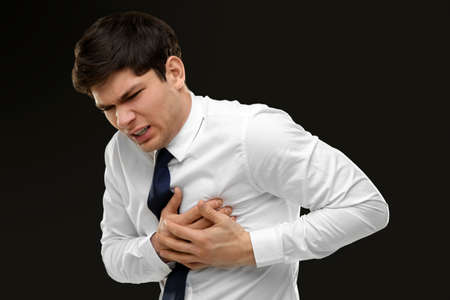 Heart attack concept. Young man suffering from chest pain on black background Stok Fotoğraf