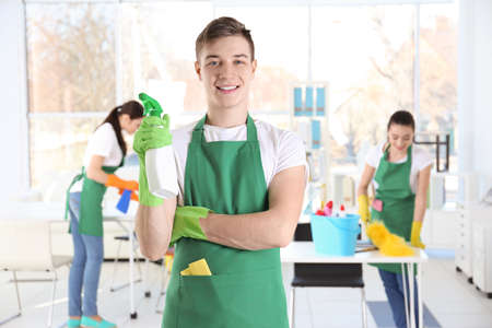 Young male cleaner at work in office Stock Photo