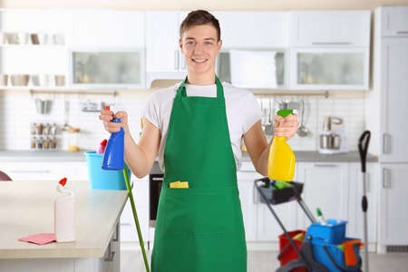 Young male cleaner at work in kitchen