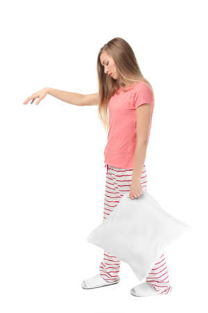 Young sleepy woman with pillow suffering from somnambulism on white background Stock Photo