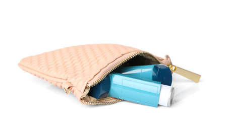 Cosmetic bag with asthma inhalers on white background Stock Photo