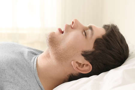 Handsome young man sleeping in bed at home Stock Photo