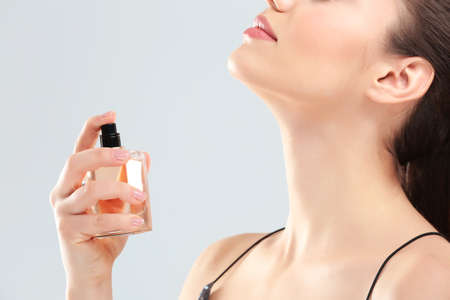 Beautiful young woman with bottle of perfume on light background Stock Photo