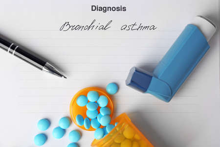 Asthma inhaler, pills and pen on diagnosis form