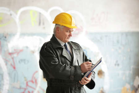 Insurance adjuster in devastated room of abandoned building