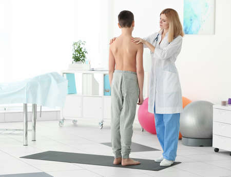 Incorrect posture concept. Physiotherapist examining and correcting boys back 版權商用圖片