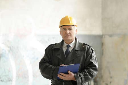 Insurance adjuster in devastated room of abandoned building Reklamní fotografie - 97732213